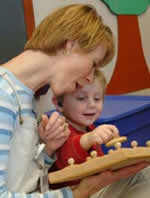 Adult assisting deaf boy
